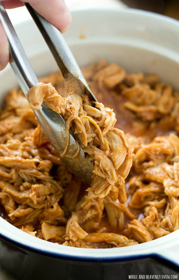 This simple BBQ pulled chicken cooks entirely in the crockpot and hungry game-day guests won't believe that it comes together with only 2 ingredients! @WholeHeavenly