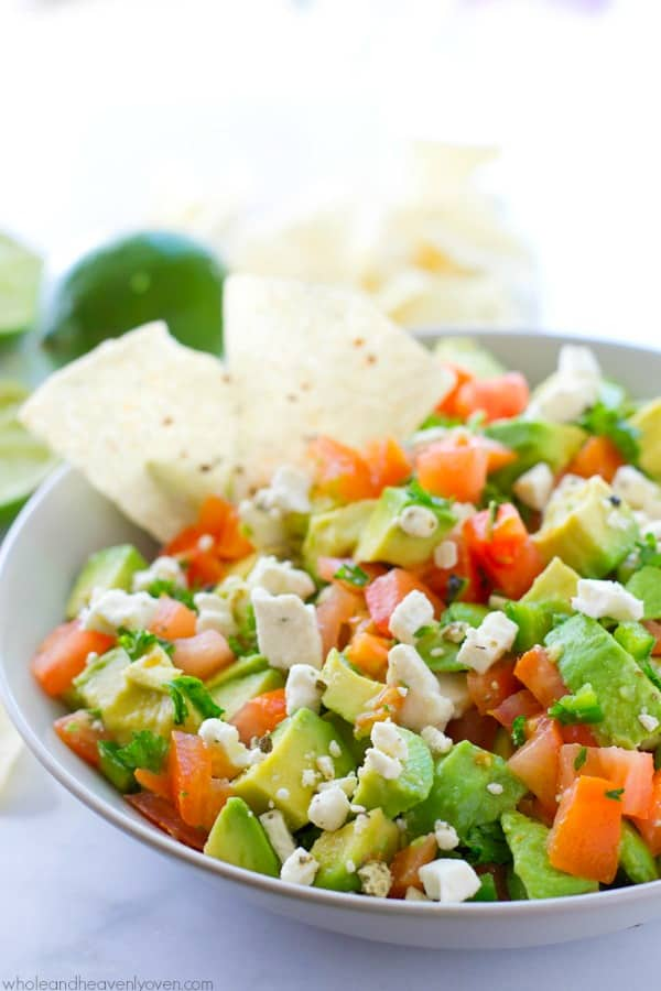 Unbelievably fresh-tasting and loaded with a plethora of flavorful greek ingredients, this easy chunky-style guacamole will quickly become your gotta-have summer appetizer! @WholeHeavenly