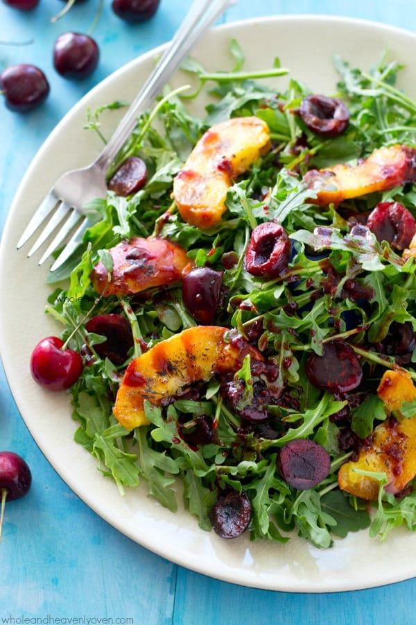 This pretty arugula summer salad is loaded to the max with sweet grilled peach wedges, juicy cherries and the most amazing raspberry balsamic dressing ever!