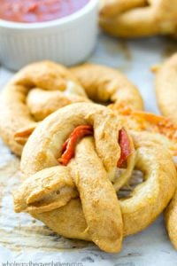 Exploding with gooey cheese and pepperoni slices, these crowd-pleasing soft pretzels are guaranteed to disappear the second you put them out!