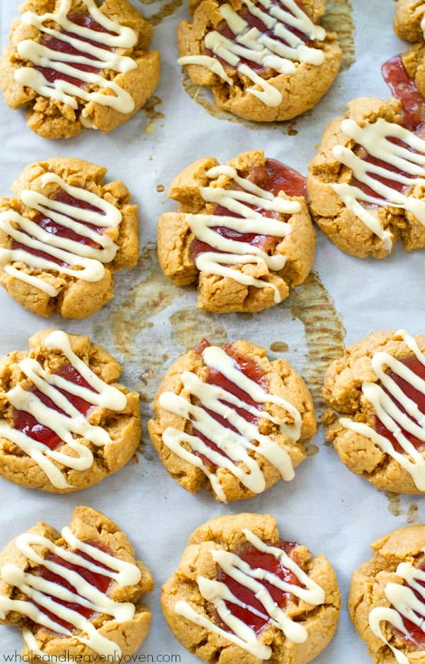 Soft and chewy peanut butter thumbprint cookies are filled with fruity jam and then drizzled to perfection with white chocolate.---Grab that cold milk! @WholeHeavenly