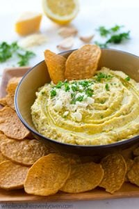 A trio of cheeses, homemade roasted garlic, and fresh herbs star in this super-easy and unbelievably smooth hummus.---It's the perfect dip for any holiday appetizer table!