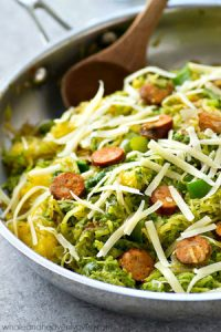 Spaghetti squash loaded with flavorful pesto and lots of sliced sausage! An easy and healthy skillet dinner with only 7 ingredients!