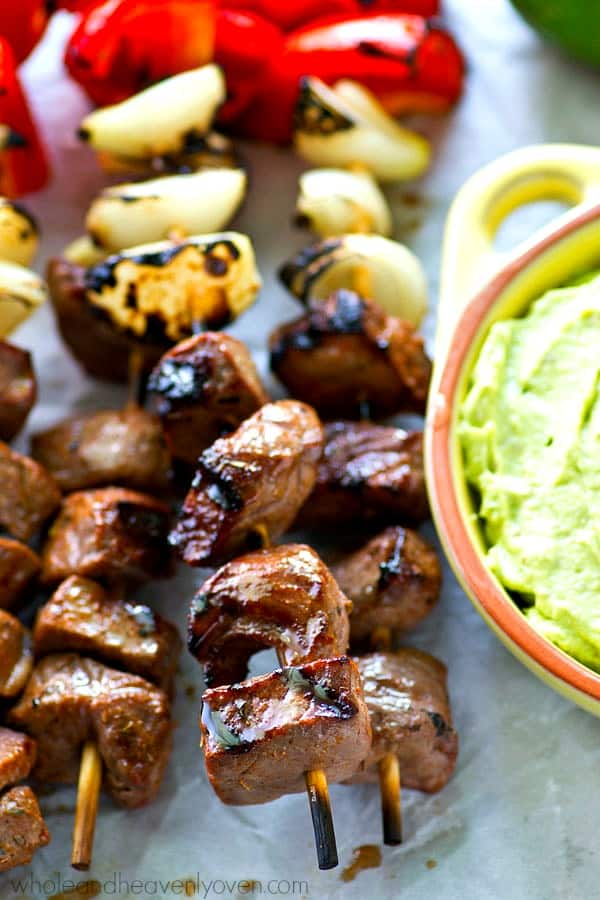 Simple grilled steak and pepper kebabs with just a little kick of spice that go perfectly with a cool and creamy avocado dip.---These steak kebabs are SO easy to make!