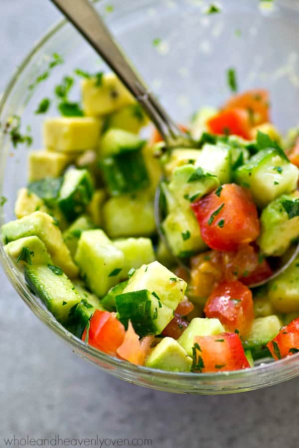 Tender tuna steaks are marinated in cilantro and lots of lime, grilled until perfectly smoky, and topped with an amazing fresh avocado cucumber salsa for one easy summer dinner!