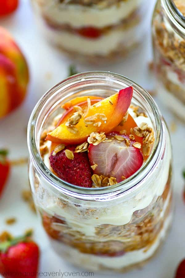 Sweet roasted peaches and strawberries layered with creamy vanilla yogurt and crunchy granola makes the ultimately easy and impressive breakfast granola parfait!