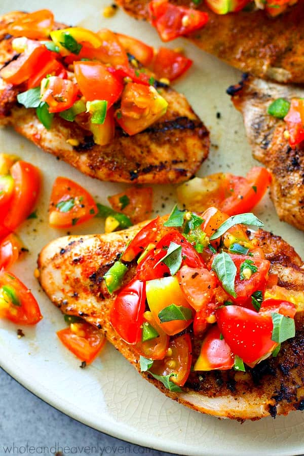 Juicy grilled chicken breasts get rubbed with a zippy cumin spice mix and topped with tons of fresh garden tomato salsa!---An easy summer dinner in less than 20 minutes.