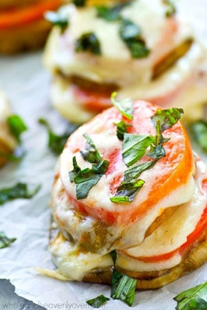 These layered caprese stacks feature fresh heirloom tomatoes, eggplant, and plenty of mozzarella cheese and fresh basil.---Ready in 15 minutes with only FIVE ingredients!