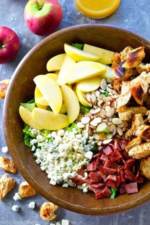 This fall-style apple salad is packed with tons of seasonal fall goodness and a tangy-sweet apple cider dressing drizzled on top brings all the amazing flavors together!