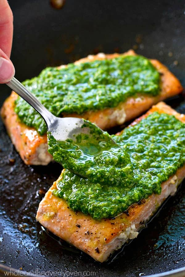 Simple pan-seared salmon is smothered in a flavorful spinach basil pesto sauce for a healthier dinner you can have ready in under 15 minutes. --- Serve this salmon with a green salad and you've got dinner done!