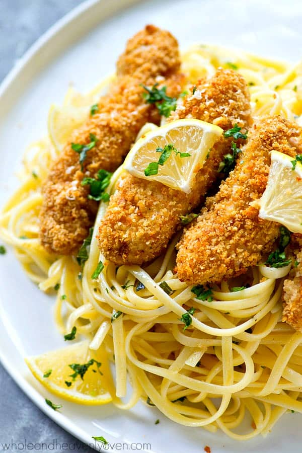 Crispy lemon Parmesan baked chicken strips and buttery herb noodles make for one unbelievably fast and easy, yet totally insanely flavorful dinner that everyone will gladly gobble up!