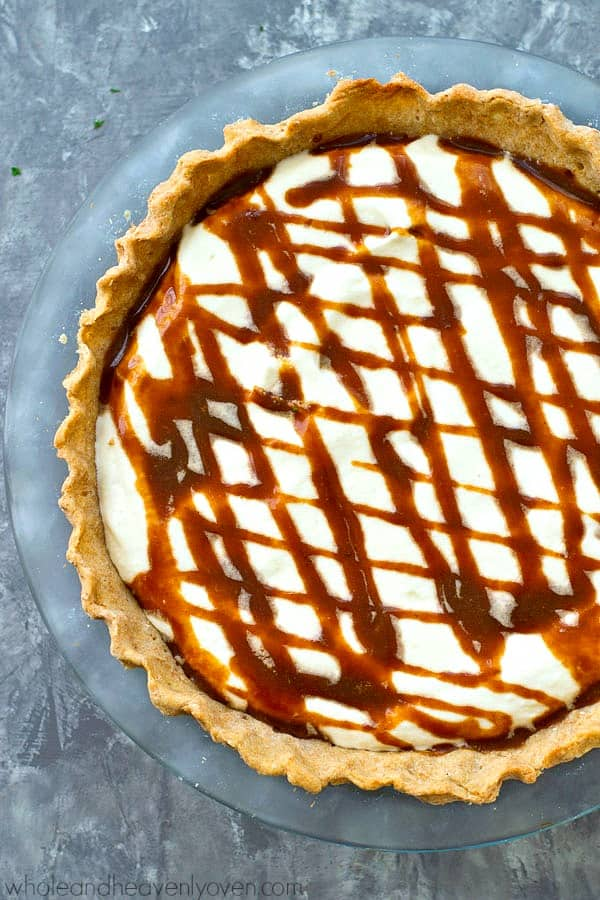 Pumpkin pie and cheesecake collide in this stunning no-bake pie that will quickly become a new tradition at your Thanksgiving dessert table! Homemade caramel sauce drizzled on top is the perfect finishing touch.