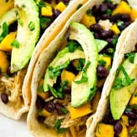 Up your taco night game with these INSANELY-easy crockpot green chile chicken tacos! The chicken is unbelievably tender and a mango black bean salsa piled on top brings tons of flavor!