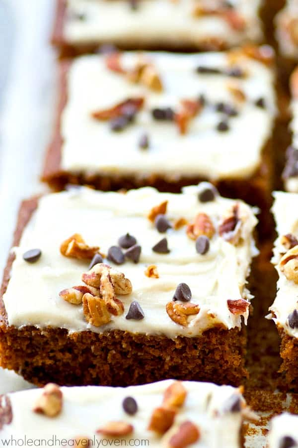 These super-soft and spicy gingerbread cake bars are loaded with gooey chocolate chips and frosted with a tangy cream cheese frosting for the easiest last-minute holiday dessert!