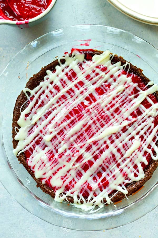 This flourless mocha chocolate raspberry pie is unbelievably fudgy and filled with a tangy raspberry sauce and drizzled with lots of white chocolate. You won't believe how easy it is to make!