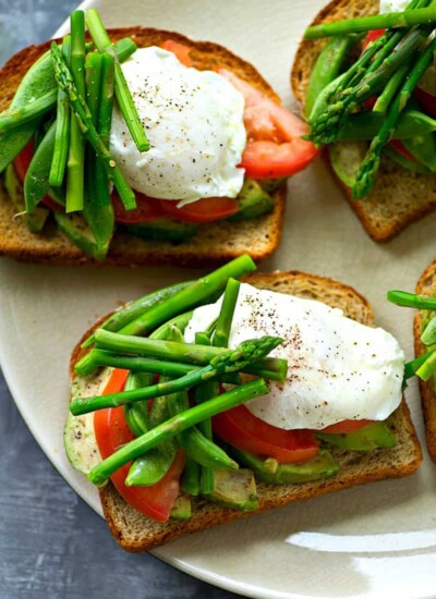 Avocado toast gets a spring upgrade!! This easy farmers market-style avocado toast is packed to capacity with spring veggies and a pretty poached egg makes it an entire breakfast-in-one!