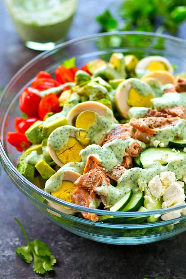 Grilled salmon, tons of fresh veggies, and an insanely flavorful cilantro lime ranch dressing make this cobb salad the ULTIMATE salad to put on the lunch or dinner rotation!