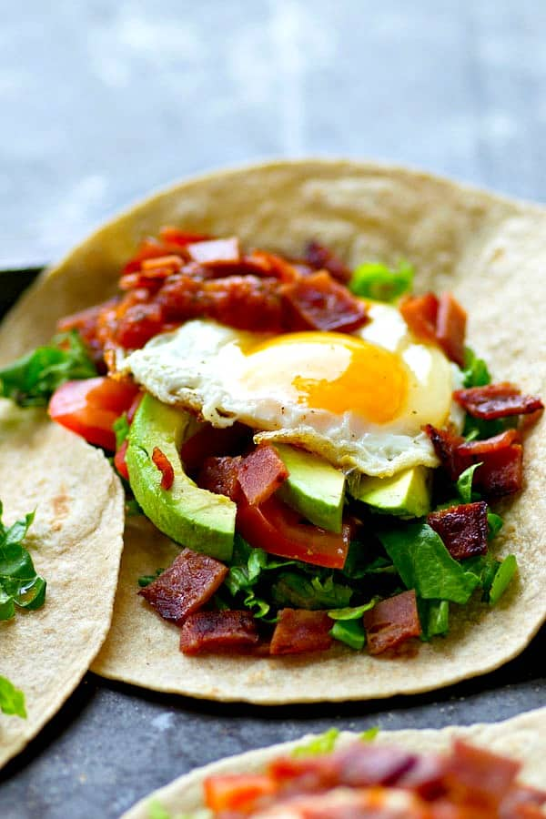The most loaded breakfast tostadas you'll ever have in your life! Everything you find in a BLT sandwich, sliced avocado, and a gorgeous fried egg on top.