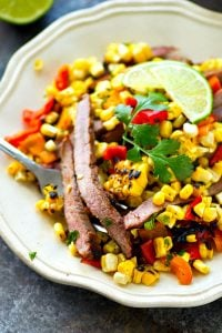 Juicy grilled skirt steak is piled high with a flavorful charred corn sweet pepper salsa and is hands down the BEST summer steak dinner you'll ever have!