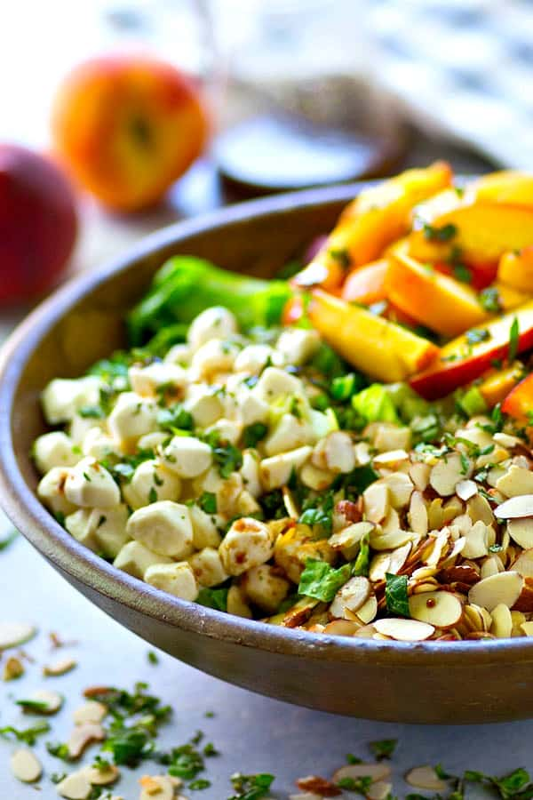 Juicy fresh peaches and a sweet 'n' tangy balsamic vinaigrette boost this killer summer caprese salad up a notch! All the best summer flavors and you can throw it together in 10!