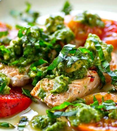 Grilled salmon and juicy heirloom tomatoes are covered in an INSANELY flavorful avocado chimichurri sauce for an easy, healthy, and flavor-packed summer dinner!