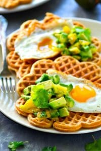 Light and crispy cornmeal cheddar waffles are topped with a beautiful fried egg and tons of avocado pico de gallo for the BEST savory twist on waffles you'll ever have!
