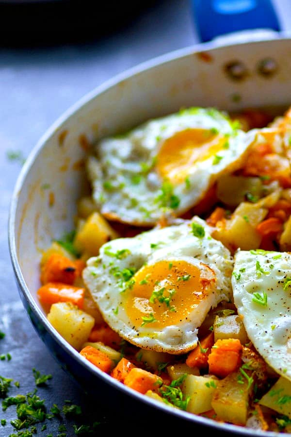 Picture-perfect fried eggs sit on top of a flavorful rainbow vegetable hash for a super-healthy, quick, and gorgeous savory breakfast!