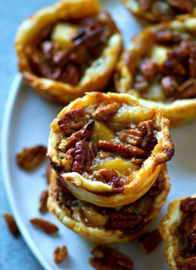 These mini caramel apple pecan pies combine the best of both pie worlds with a caramel apple pie filling and a sweet pecan pie topping.---They're nearly impossible to stop eating!