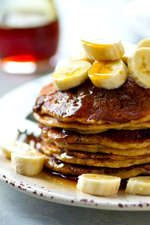 Thick and fluffy banana buttermilk pancakes are generously coated in a homemade cinnamon crunch topping for the ultimate pancake combo.---you will not be able to stack these high enough!