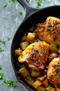 Skillet Honey Garlic Chicken Thighs - Juicy honey garlic chicken thighs and crispy roast potatoes are seared and baked in the most FLAVORFUL honey garlic sauce in this no-fuss one skillet dinner!