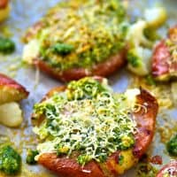 Crispy smashed red potatoes are drizzled in a flavorful basil pesto and topped with lots of Parmesan cheese for an easy and addicting side dish!