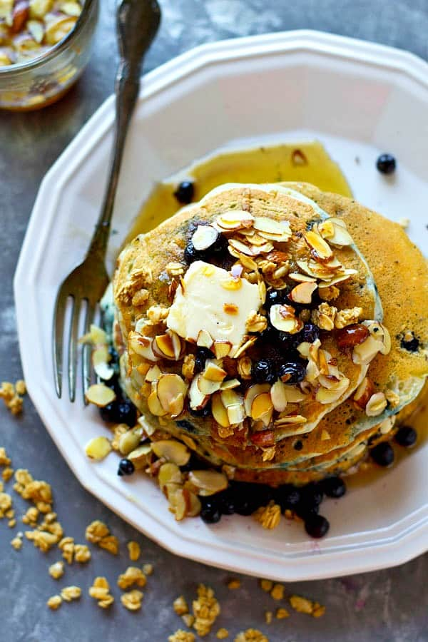 Juicy blueberries and crunchy granola are the ultimate duo in these SUPER thick and fluffy blueberry granola pancakes! Drizzle them with tons of almond syrup for a breakfast winner!