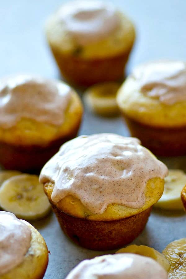 Incredibly soft banana cream cheese muffins have a tangy cream cheese surprise in the center and they're covered to perfection with chai-spiced glaze.---Make a double batch of these muffins!