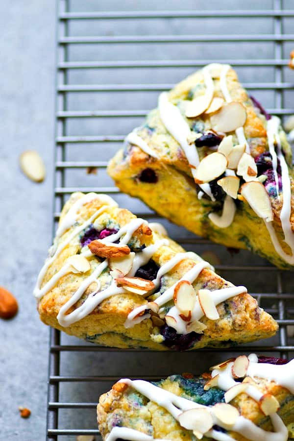 Flaky blueberries 'n' cream almond scones are jam-packed with juicy blueberries, toasty almonds, and drizzled with a rich vanilla glaze.---just try to eat only one of these addicting scones!