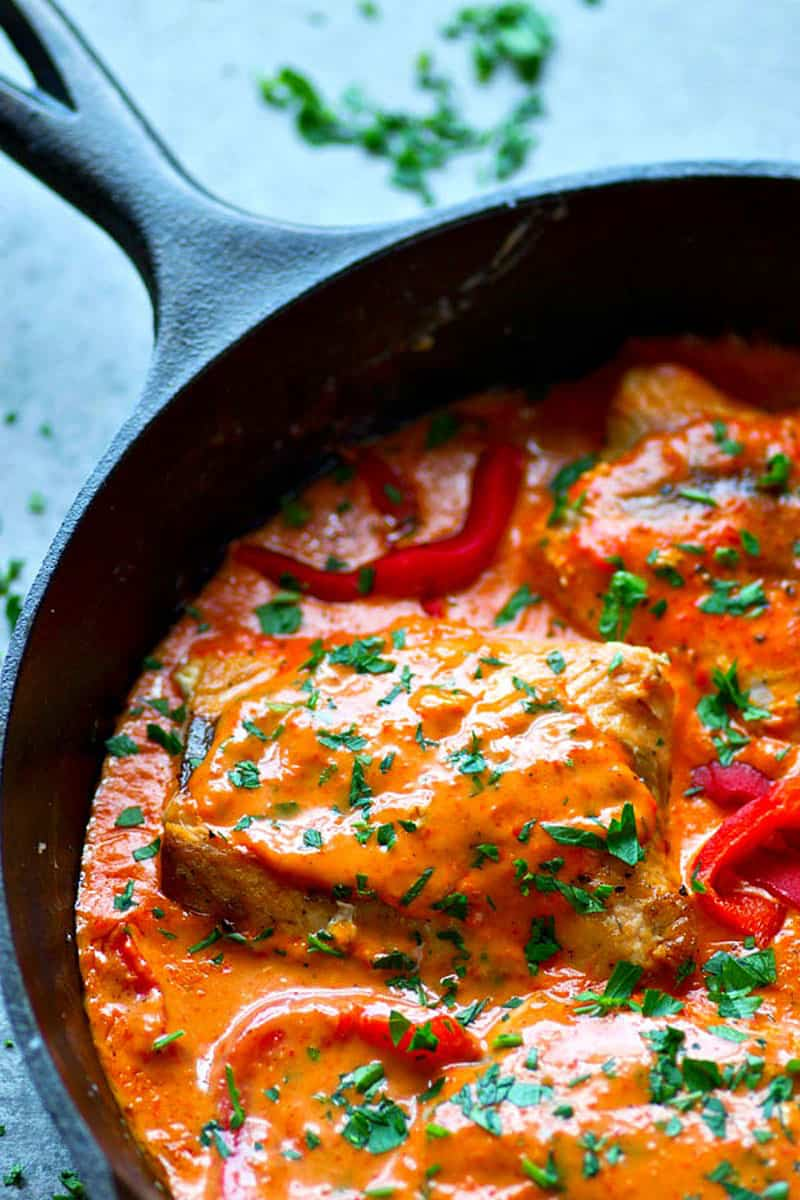 Melt-in-your-mouth pan-seared salmon is covered in an INSANELY flavorful roasted red pepper sauce for a quick, flavor-packed dinner! Serve it over rice or noodles.