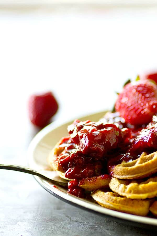 Crispy, rustic cornmeal waffles are topped with the BEST homemade strawberry preserves for the best summer breakfast you'll ever have.