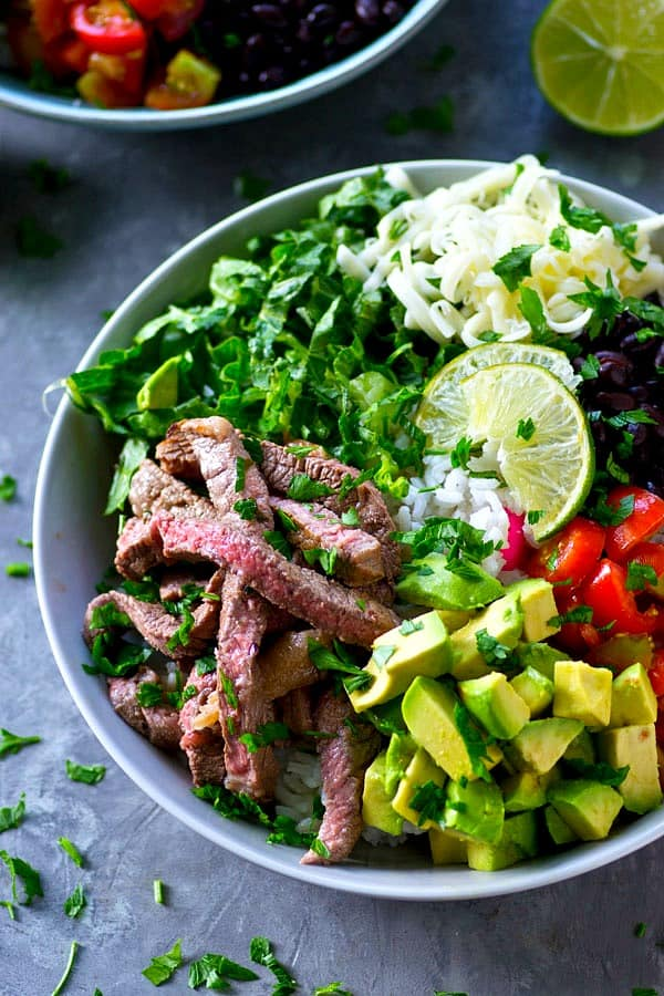 Juicy, flavorful cilantro lime grilled steak and all the burrito 'fixins come together in these loaded grilled steak burrito bowls and it'll be on the table in only an hour!