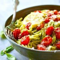 Flavor-packed lemon basil pesto spaghetti is topped with juicy bursting tomatoes for the BEST summer pasta side that's perfect alongside grilled chicken or fish.