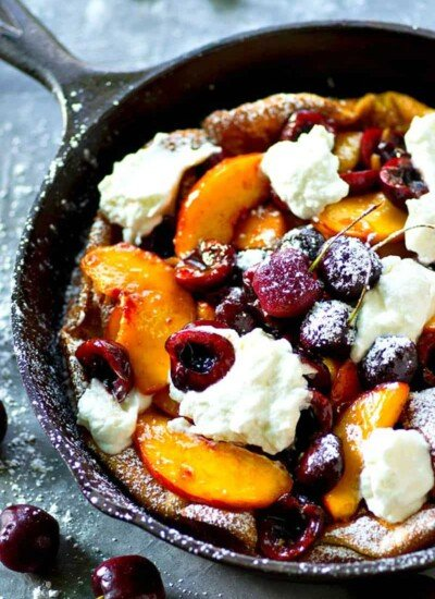 Fluffy honey whipped cream and juicy summer cherries and peaches are piled high into this summery cherry peach dutch baby that's ready in 30 minutes flat!