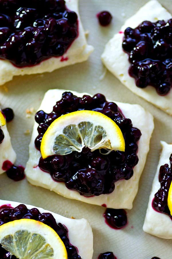 No-bake blueberry lemon cheesecake bars made ENTIRELY in the fridge with a soft graham cracker crust, a creamy lemon cheesecake filling, and a sweet blueberry sauce on top.