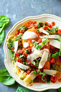 Braised in a rich Italian tomato sauce with spinach and plenty of herbs, this Italian tomato spinach braised chicken practically cooks itself and it's the perfect dinner piled on top of hot noodles.