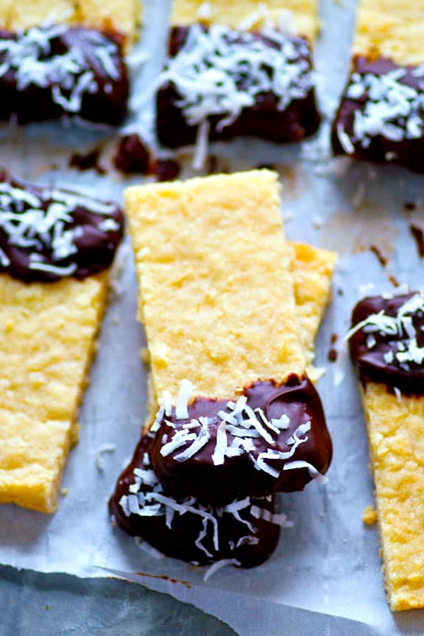 Soft, buttery coconut shortbread bars are dipped in melted chocolate and rolled in coconut flakes for the ultimate holiday cookie bar!
