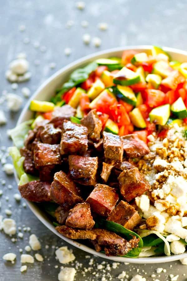 Juicy greek yogurt marinated steak, a tangy honey balsamic dressing, and all the Greek salad fixins' collide in this beautiful, meal-in-one Greek steak salad!