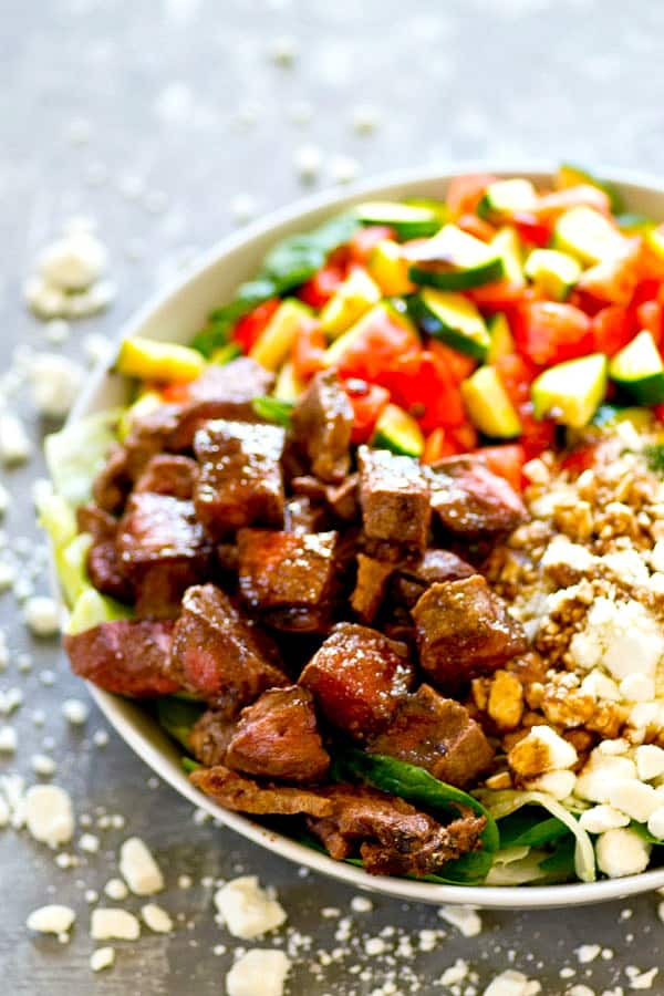 Juicy greek yogurt marinated steak, a tangy honey balsamic dressing, and all the Greek salad fixins' collide in this beautiful, meal-in-one Greek steak salad!