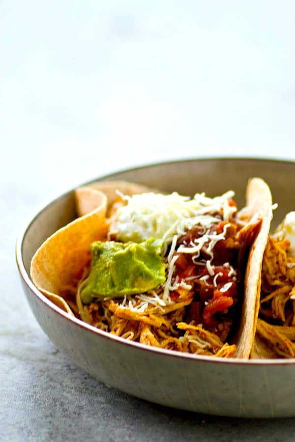 Homemade taco seasoning and a quick cook in the instant pot are the secrets behind this INCREDIBLY tender and flavorful taco shredded chicken! Perfect for topping tacos and salads!