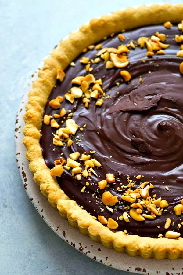 A rich chocolate ganache filling and a soft, chewy peanut butter cookie crust are the most INSANE combo in this luscious chocolate ganache tart.