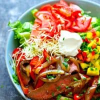 Incredibly tender grilled beef, a spicy mango pico de gallo, and all the fajita fixings you love collide in this jam-packed grilled beef fajita salad! You'll never have a boring dinner salad again.