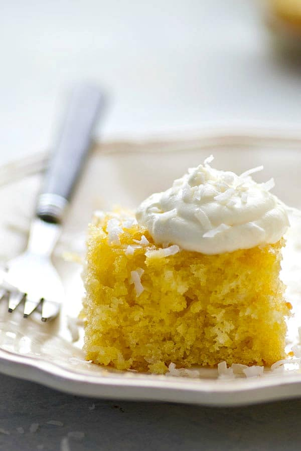 This pina colada poke cake is loaded with tons of coconut and brushed with a sweet pineapple glaze for the most INSANELY soft and moist poke cake ever!