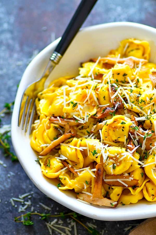 Flavorful shiitake mushrooms are incredibly good paired with a rich garlic butter sauce, sharp Asiago cheese, and lots of cheese-filled tortellini in this killer garlic butter Asiago tortellini skillet!