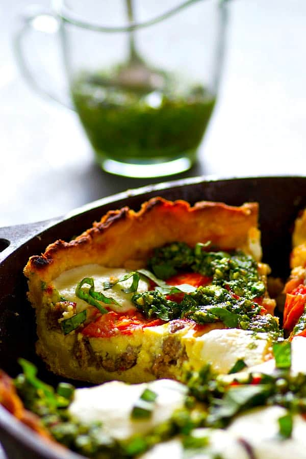 A fresh homemade basil pesto and all the caprese fixins' are a match made in brunch heaven in this skillet basil pesto sausage caprese quiche! Cut BIG slices of this luscious quiche for best results.